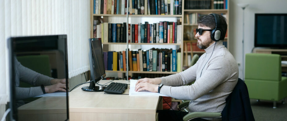 man with sunglasses and headphones sitting at a computer